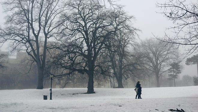 People walk in Brooklyn's Fort Greene Park in the fog on Feb. 21, 2014, in New York City.  After a mild weekend, frigid air will make its way to the Northeast this week.