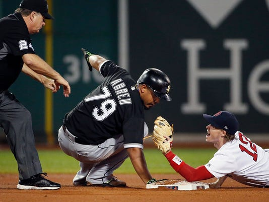 Second base umpire Jerry Layne calls safe as Boston Red Sox's Brock Holt (12) protests after tagging Chicago White Sox's Jose Abreu during the eighth inning of a baseball game in Boston, Saturday, Aug. 5, 2017. The call was overturned after the Red Sox challenged the play. (AP Photo/Michael Dwyer)
