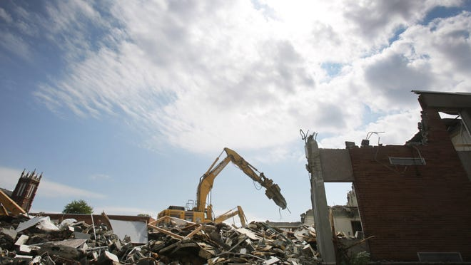Crews from Eslich Wrecking demolish the east end of the former Washington High School along Oak Avenue SE on Tuesday. The site is being renovated into Massillon City Schools' operations facility.