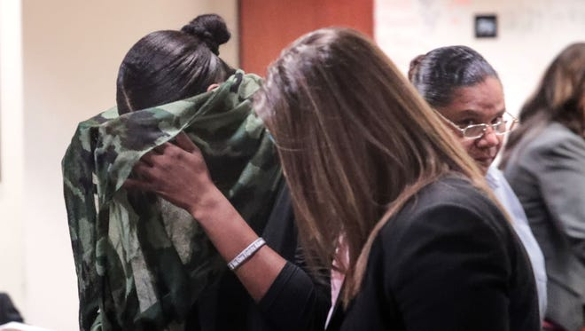 Brandi Perry covers her face as she exits the courtroom with sister-in-law Sandra Johnson, back right, after a court appearance at the Larson Justice Center in Indio on Wednesday, December 13, 2017. The two women are accused of embezzling from the city of Rancho Mirage.