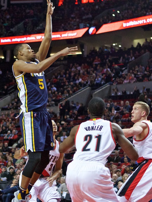 Utah Jazz guard Rodney Hood, left, shoots over Portland Trail Blazers center Mason Plumlee, right, and forward Noah Vonleh, center, during the first half of an NBA basketball game in Portland, Ore., Wednesday, Jan. 13, 2016. (AP Photo/Craig Mitchelldyer)
