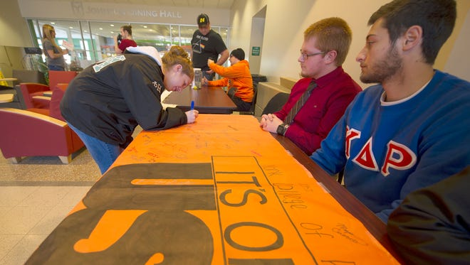 Darryl Andreas, rear right, and Ryan Thal, with the Kappa Delta Rho fraternity at York College., look on as freshman Allie Bernstein signs their banner against sexual assault in the student union building. York College joined the state's new It's On Us PA campaign to end campus sexual assault.