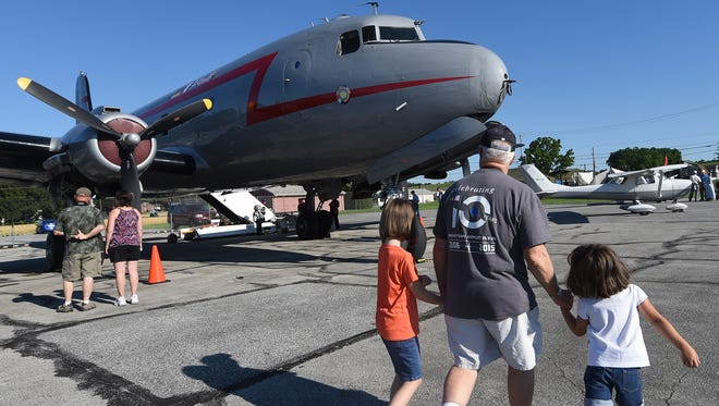 Edward Temos of York, New Salem takes his granddaughters, Sofia Przygrodzki, 7, left, and Cecelia,4, to get into a Douglas C 54-R5D at the York Airport Aviation Days.