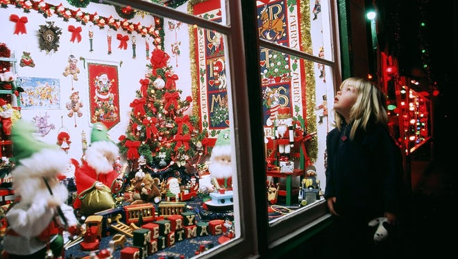 A girl peers into a window of one of the many small buildings containing Christmas scenes.