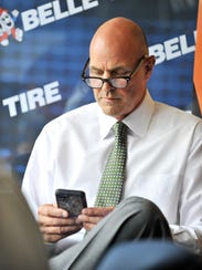 Kirk Gibson checks his phone before Thursday's game