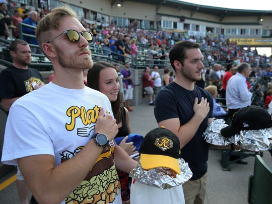 Cory Gomes, Jamie Thompson and Mike Barry stand for the national anthem during the Rochester Red Wings' Plates Night. FROM MAX: O'er the land of the free and the home of the plates. The fork over the heart makes this photo for me.