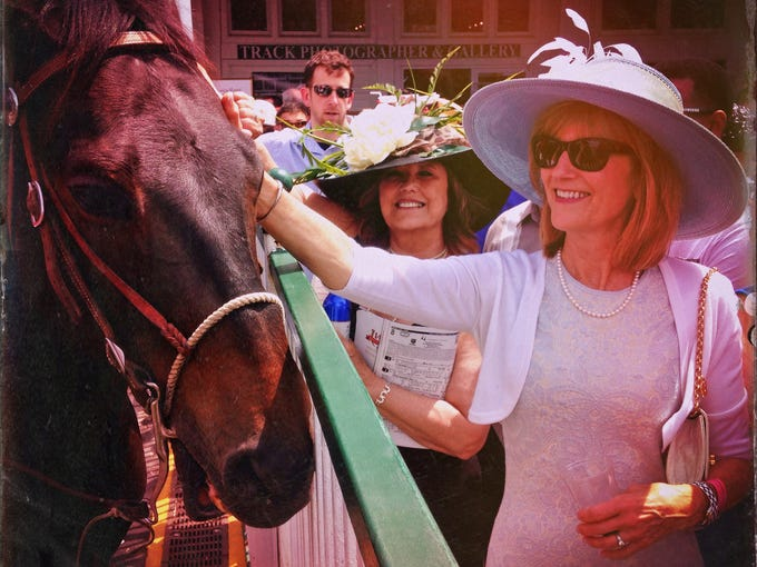 Terrie Cummins, right, pets an outrider's horse Saturday near the paddock area at Churchill Downs before the start of race eight, The Eight Belles. May 3, 2014
