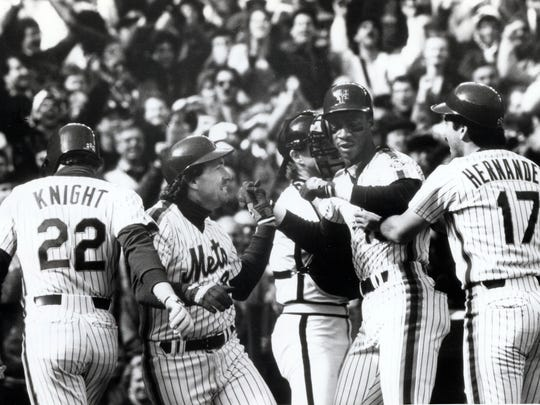 FILE from Oct. 11, 1986 in Flushing, N.Y. for Mets and Astros playoff. Darryl Strawberry, center, is congratulated by teammates after hitting a three run homer.