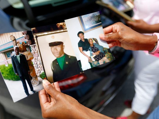 Rosalyn Lewis holds photos of her dad C.L. Lewis who was killed in a car accident in 2015.