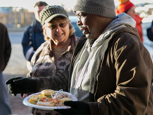 Ronald Dropthmore receives delicious food to eat during the fourth annual Temple Beth-El Christmas Breakfast at Camp Hope on Thursday, December 24, 2015. Standing in the background is volunteer and temple member Avis Lewis.