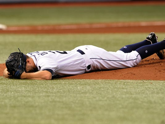 Tampa Bay Rays starter Jake Odorizzi lays prone on the mound after he was hit in the right leg by a line drive from Boston Red Sox's Eduardo Nunez during the fifth inning of a baseball game Wednesday, Aug. 9, 2017, in St. Petersburg, Fla. (AP Photo/Steve Nesius)