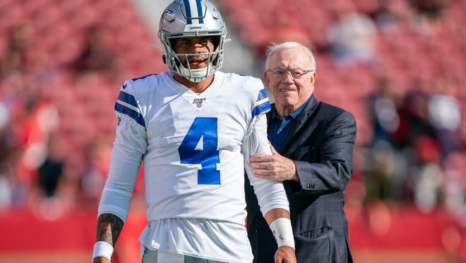 Dallas quarterback Dak Prescott, chatting with Cowboys owner Jerry Jones before a preseason game in 2019, will be paid $31.4 million this season if he plays under the franchise tag rather than a long-term deal.