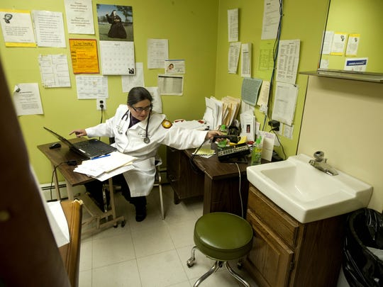 Dr. Lesly D'Ambola does paperwork in between appointments in one of the exam rooms at St. Luke's Catholic Medical Center in Camden in 2014.
