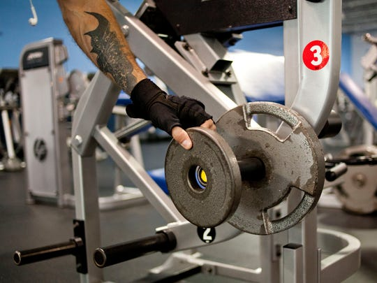 Glenn Taylor of Port Huron puts weights on a curling machine September 25, 2014 at Cutting Edge Health and Fitness in Port Huron.