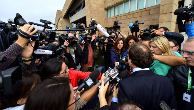 Meredith Kercher's family lawyer Francesco Maresca (back right), speaks to the press as he arrives at the Florence's courthouse on Sept. 30, 2013.