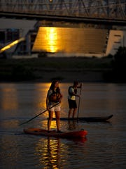 Milford residents Emily White and Robby Hanson, of Roads, Rivers, and Trails outdoor retailer, paddle on the Ohio River during the early morning kick off to Paddlefest in 2013.