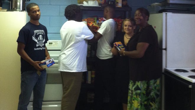 Far right, Lafronda Blunt with family members from New Albany, Indiana in the kitchen of Emmanuel Church of Christ in Dickson.