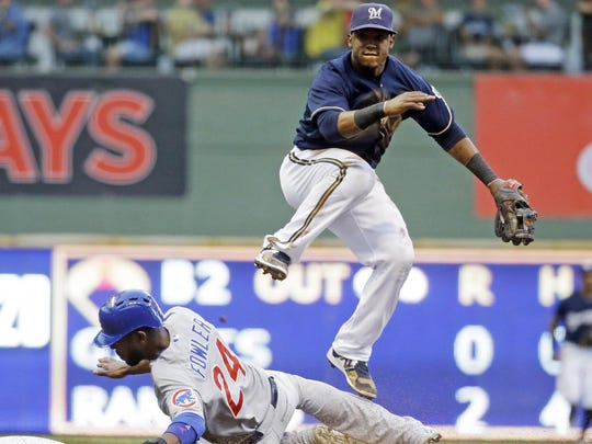Jean Segura of the Milwaukee Brewers leaps over Dexter Fowler of the Chicago Cubs to turn a double play during the fifth inning on Saturday in Milwaukee.