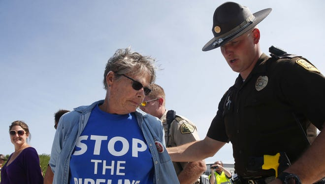 Some of the more than 100 protesters were placed under arrest on trespassing charges on Wednesday, Aug. 31, 2016, in Boone, Iowa, as they gathered to voice their opinion against the development of the Bakken Pipeline during a rally on four of the entrances to the pipeline construction site.