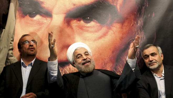In this June 1, 2013, file photo, new Iranian President Hasan Rowhani, a former top nuclear negotiator, center, gestures to his supporters at a rally in Tehran during his presidential campaign.