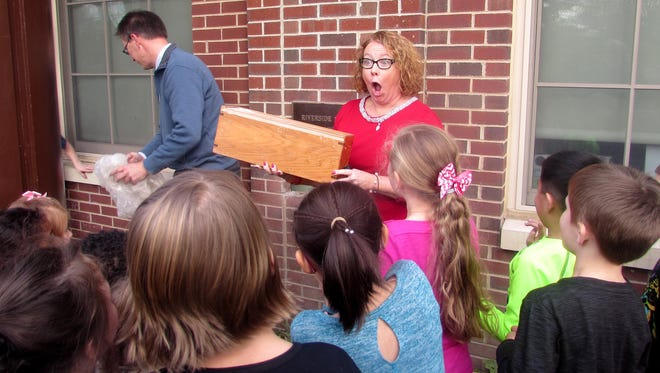 Riverside Elementary School Principal Heather Donovan shows off a time capsule from 1991 after it was removed Thursday from the outer wall of the school.