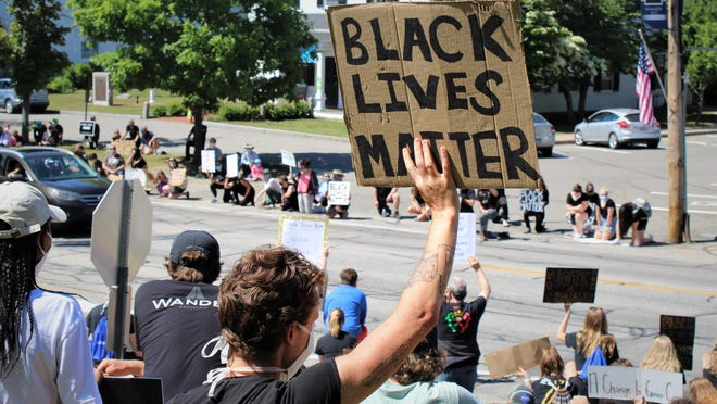 "Protesters hold ""Black Lives Matter"" signs along York Street in York, Maine, on Sunday, June 14. They circulated a petition calling on the York School Department to improve its Black history curriculum and better support students of color."