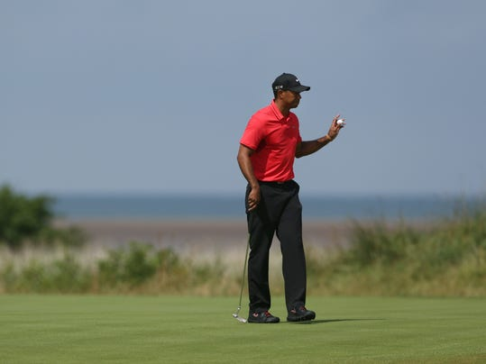 Tiger Woods of the US holds up his ball after putting out on the 13th green during the final round of the British Open Golf championship at the Royal Liverpool golf club, Hoylake, England, Sunday July 20, 2014. (AP Photo/Jon Super)