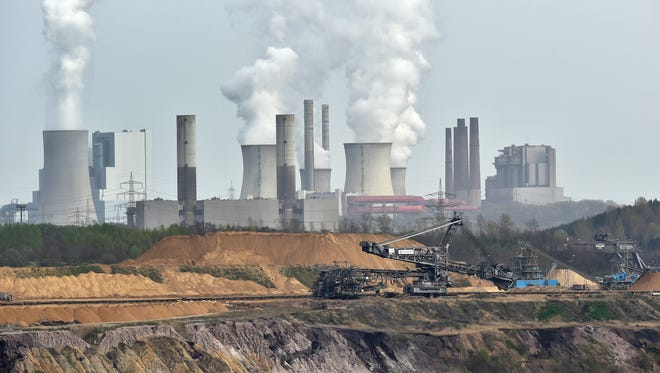 In this picture taken Thursday, April 3, 2014, giant machines dig for brown coal at the open-cast mining Garzweiler in front of a smoking power plant near the city of Grevenbroich in western Germany. After concluding that global warming is almost certainly man-made and poses a grave threat to humanity, the U.N.-sponsored expert panel on climate change is moving on to the next phase: what to do about it. The Intergovernmental Panel on Climate Change, or IPCC, will meet next week in Berlin to chart ways for the world to rein in the greenhouse gas emissions that scientists say are overheating the planet. (AP Photo/Martin Meissner)