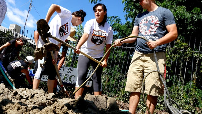 Jiovona Sandoval, left, Zoe Selph, and Brian Umbarger, all of Aztec, move dirt and debris to a pile Aug. 27, 2015, after a flood at the Aztec Museum.