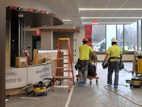 Mike Walz, left, and Andrew Laudenbach of Custom Drywall in St. Paul move equipment through the under-construction new-patient intake area that's part of a St. Cloud Hospital emergency department upgrade. To the left is the area that will serve as the reception desk.
