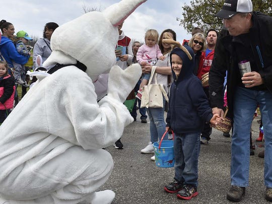 With a little coaxing from his grandfather, Bill Peters of Hudson, Billy Hoff of Pecatonica, Illinois, greets the Easter Bunny for the first time during last year's egg hunt at Waterfront Park in Sister Bay.