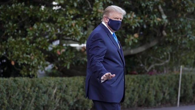 President Donald Trump waves to members of the media as he leaves the White House to go to Walter Reed National Military Medical Center after he tested positive for COVID-19, Friday, Oct. 2, 2020, in Washington.