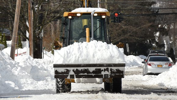A truck picks up snow along Orchard Place in the City