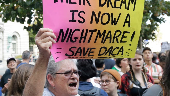 Judy Weatherly, a supporter of the Deferred Action for Childhood Arrivals (DACA), holds up a sign during a protest outside of the Federal Building in San Francisco, Tuesday, Sept. 5, 2017. President Donald Trump on Tuesday began dismantling DACA, the government program protecting hundreds of thousands of young immigrants who were brought into the country illegally as children. (AP Photo/Jeff Chiu)