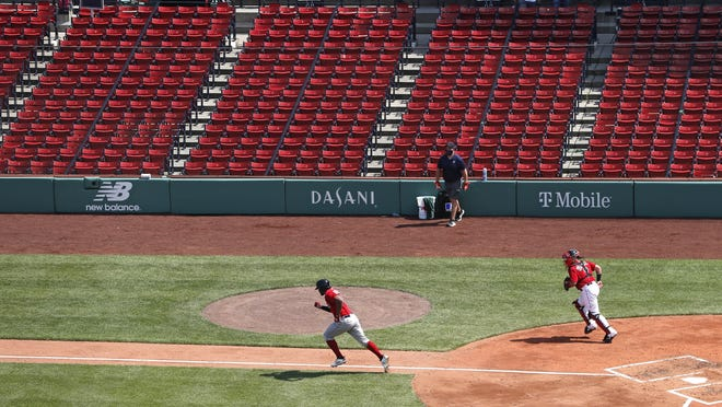 Boston's Xander Bogaerts dashes down the first base line in front of empty stands on his ground out during an intrasquad baseball game on Thursday.