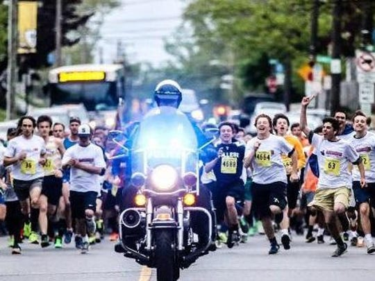 A policeman on motorcyle leads runners at the starting line in the Lt. Joe Szczerba '85 Memorial 5K. Szczerba, a New Castle County police officer, was killed on duty in 2011.