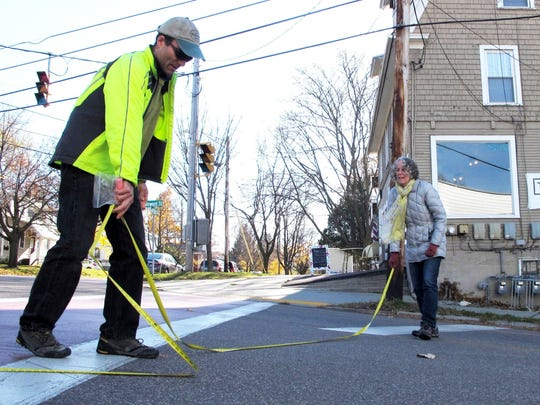 Burlington South End residents and walk/bike advocates Jason Van Driesche, left, and Julie Campoli measure and chalk-line traffic lanes Saturday at Howard and St. Paul streets. The two were among about 20 residents who gathered to discuss possible safety upgrades to the Howard Street intersection. Photographed on Saturday, Nov. 12, 2016.