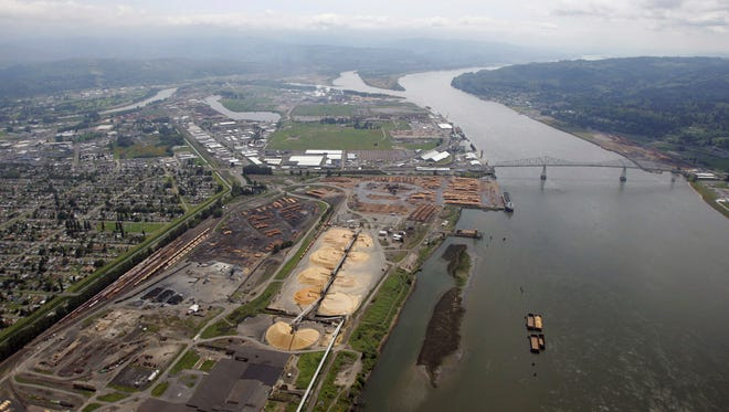 FILE--In this May 12, 2005, file photo, timber processing facilities line the banks of the Columbia River at Longview, Wash., near the Lewis and Clark Bridge. Six Western states and several national industry groups have lined up against Washington state in a legal battle over its decision to reject permits for a massive proposed coal-export terminal on the Columbia River. (AP Photo/Elaine Thompson, File)