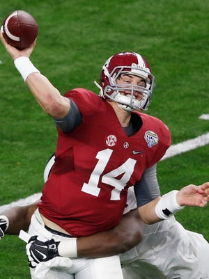 Alabama Crimson Tide quarterback Jake Coker (14) is tackled by Michigan State Spartans defensive lineman Malik McDowell (4) during the third quarter in the 2015 CFP semifinal at the Cotton Bowl at AT&T Stadium.