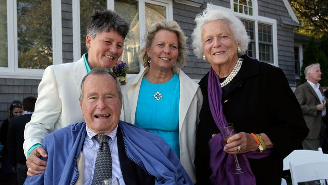 In this Sept. 21 photo, former President George H.W. Bush, front left, former first lady Barbara Bush, right, pose for photos after wedding of longtime friends Helen Thorgalsen, center, and Bonnie Clement, in Kennebunkport, Maine.