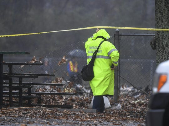 An investigator works the scene of a small plane crash in a city park which killed all on board, Thursday, Dec. 20, 2018, in northwest Atlanta.