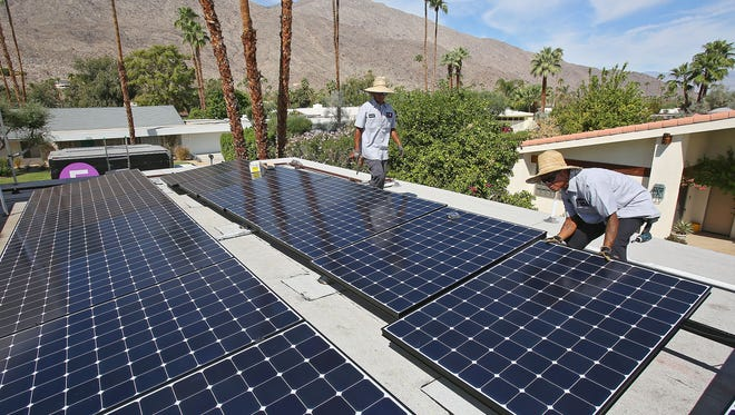 Hot Purple Energy solar technicians Gabe Rueda, right, and Enrique Perez install solar panels on the roof of a home in south Palm Springs on Sept. 28, 2015.