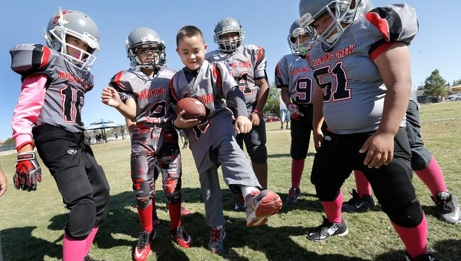 Alexander Resurreccion, 9, center, learns an endzone dance from members of the Working Crew football team Saturday after running a touchdown at Ponder Park. Resurreccion is a member of the Miracle Dream League youth football organization.