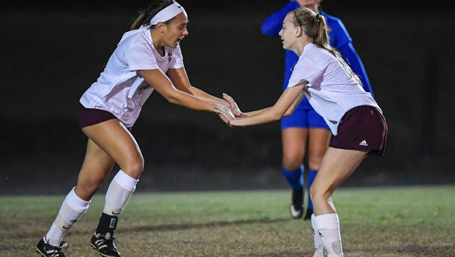 Henderson's Brooke Higginson (10) (left) congratulates teammate Isabella McChessney (23) after scoring a second period goal as Henderson County plays Caldwell County in the Girls 2nd Region final played at Madisonville North Hopkins High School in Hanson Thursday, October 19, 2017.