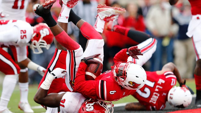 University of Louisville's Eli Rogers (6) dives in for the touchdown under pressure from N.C. State's Germaine Pratt (31) during the first quarter of play at Papa John's Cardinal Stadium in Louisville, Kentucky.       October 18, 2013