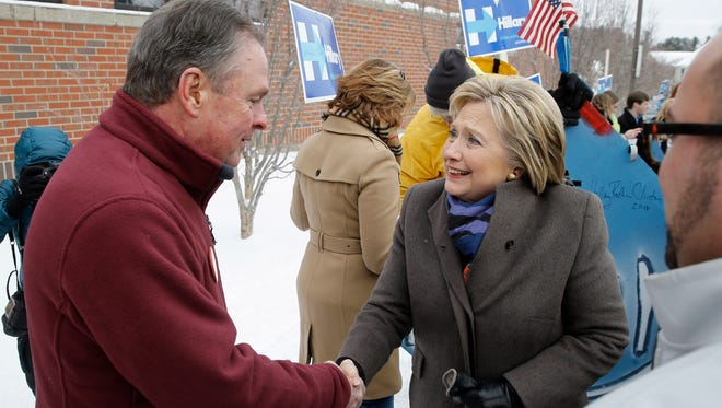 Hillary Clinton speaks with Frank Fiorina, husband of Republican presidential candidate Carly Fiorina, as they campaign outside a New Hampshire polling place on Feb. 9, 2016, in Derry, N.H.