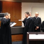 Mike Bosnic (center) was sworn into office Dec. 11 as a magistrate for the 52-1 District Court in Novi by Judge Robert Bondy.