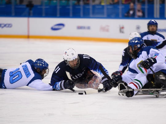 Tyler Carron, middle, battles for the puck during the Paralympics. He helped the USA win its third gold medal in a row.
