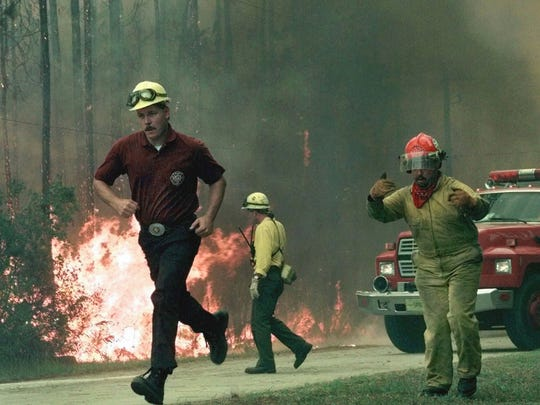 Firefighters call for more equipment as a firestorm, whipped by strong winds, moved toward several homes in the Rima Ridge area northwest of Ormond Beach on July 2, 1998.