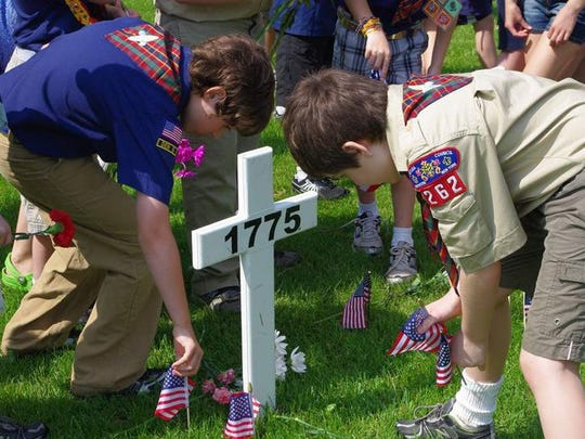 Scouts plant American flags at Webster Rural Cemetery during a Memorial Day ceremony in 2011.
